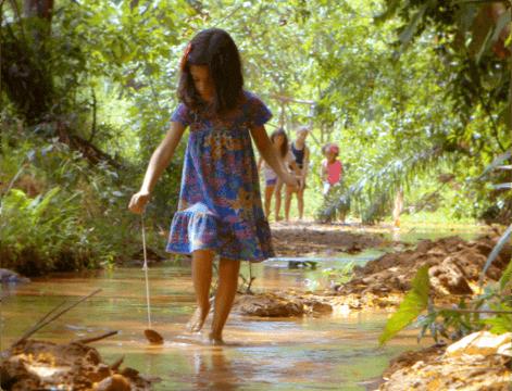 Chica en medio de la naturaleza jugando con una hoja de árbol mientras atraviesa un charco