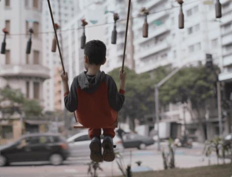 Niño sentado en el columpio en un centro urbano
