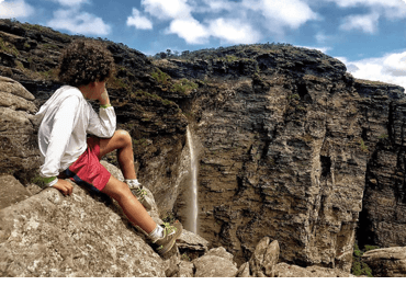 Niño sentado en la cima de la roca admirando la naturaleza